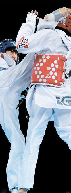 204カ国で8000万人が楽しむテコンドーがオリンピックの中核競技に分類された。写真は昨年8月に開かれたロンドン五輪テコンドー男子58キロ級準々決勝で対戦する韓国のイ・テフン(左)とエジプトのタメール・バユミ。