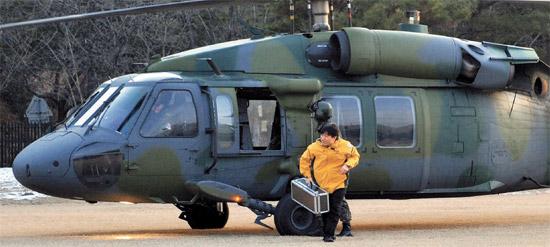 13日、韓国原子力安全技術院の研究員が陸軍のヘリコプターで移送した放射性物質が入ったかばんを研究棟に移している。