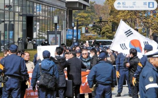 島根県が主催した「竹島の日」行事が開かれた22日、行事場所の島根県民会館の外で、独島守護全国連帯など韓国市民団体会員が日本の警察に囲まれながら太極旗を持って抗議デモを行っている。