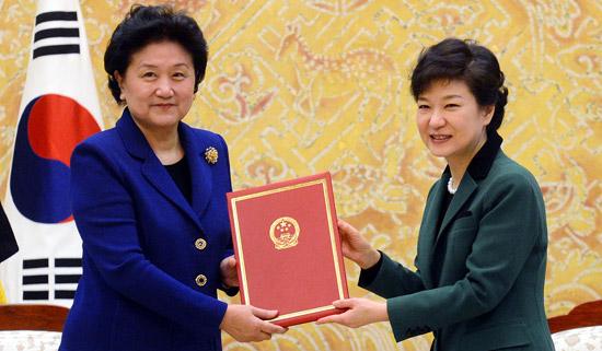 朴槿恵(パク・クネ)大統領(右)が25日、青瓦台で、劉延東中国国務委員から胡錦濤国家主席と習近平副主席の親書を受けている。