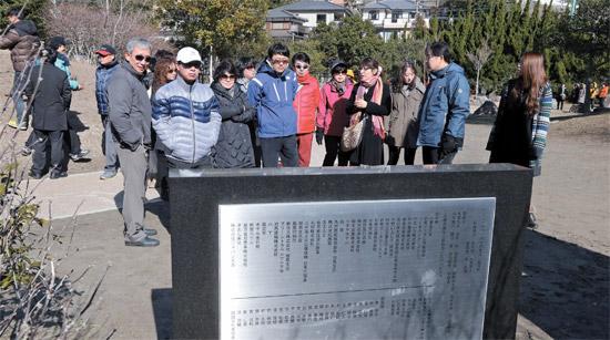 先月26日、対馬を訪問した韓国人観光客が厳原にある徳恵翁主結婚記念碑の前でガイドの説明を聞いている。