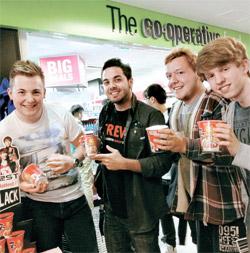 英国ロンドンのスーパーマーケットチェーン店『ザ・コーポレーション』で最近開かれたサンプリング行事で、現地の人たちが農心英国法人が無料で配った辛ラーメンカップラーメンを持って笑顔を見せている。(写真=農心)