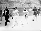 1936年8月9日、ベルリン五輪マラソン競技の表彰式場に向かう金メダリストの孫基禎と銅メダリストの南昇竜。胸に日章旗を付けている。写真の原本に説明はない。