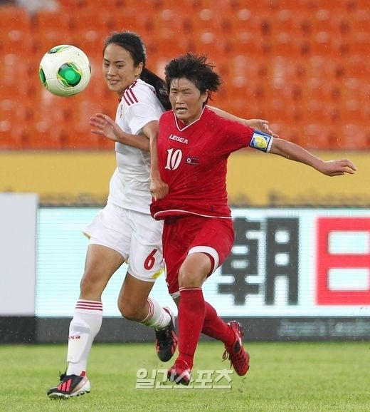 北朝鮮のラ・ウンシムの突破を中国のジェン・インがユニフォームを掴んで阻んでいる。