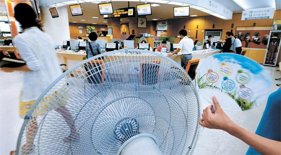 政府・公共機関が冷房を止めた12日午後、ソウル・鍾路区庁の総合請願室ではエアコンの代わりに大型扇風機が稼動している。