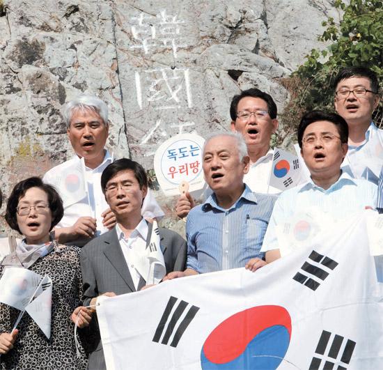 8・15光復節(解放記念日)を2日後に控えた13日、独島を訪問したキム・ハンギル民主党代表(前列右から2人目)が独島警備隊員を激励した後、「韓国領」と刻まれた岩の前で太極旗を持って愛国歌を歌っている。党指導部ら所属議員約20人と一緒にヘリコプターで独島を訪問したキム代表は「最近の日本の右傾化と軍国主義復活の動きに対し、厳重に警告する」と述べた。[独島=国会写真記者団]