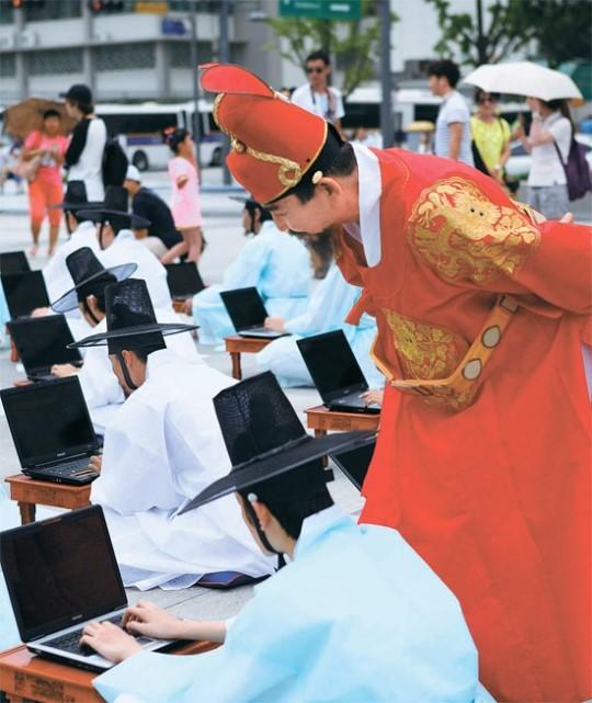 18日午後、ソウル光化門(クァンファムン)広場で袞龍袍(コンリョンポ、国王が着用する韓服)を着た王様が、ノートブックパソコンを使っている高官たちを見回っている。