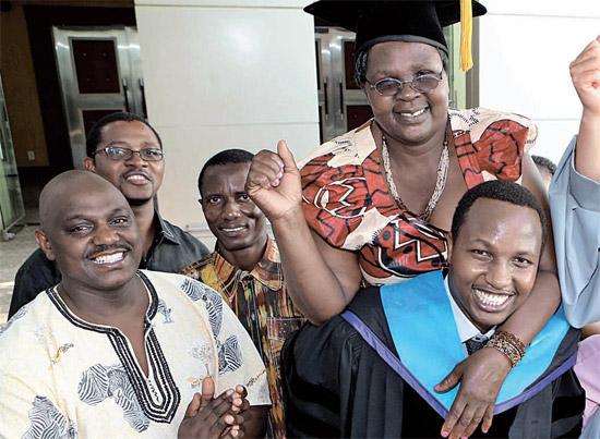 20日、釜山(プサン)の高神(コシン)大学で博士学位をもらったケニアのマサイ族出身ベンソン・カマリさんが故郷から来た母親を背負って卒業の喜びを分かち合った。