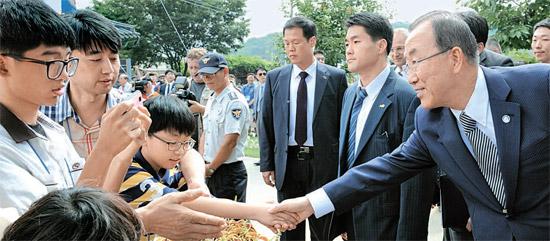 25日、故郷の忠清北道陰城郡(チュンチョンブクド・ウムソングン)ヘンチ村を訪問した潘基文(バン・ギムン)国連事務総長が歓迎に出てきた学生と握手している。(写真=陰城郡)
