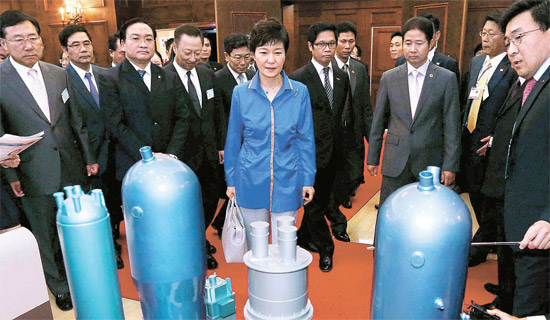 朴槿恵大統領が8日にハノイで開かれた韓国・ベトナム経済協力懇談会の会場入口に展示された韓国型原子炉模型を見ている。左からキム・ギムン中小企業中央会長、ひとりおいてベトナムのホアン・チュン・ハイ副首相、朴容晩大韓商工会議所会長、尹相直産業通商資源部長官、朴大統領、ベトナム商工会議所ブー・ティエン・ロック会長。