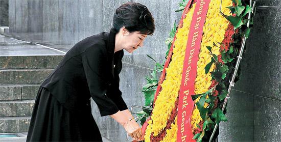 9日、ハノイにあるホー・チ・ミン元国家主席の墓地を訪れた朴大統領が、墓地の入口で「大韓民国大統領 朴槿恵」と書いたリボンの端を弔花に付けている。