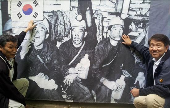 元鉱夫のファン・ソンボン館長(左)とキム・ヨンギル・ドイツ連邦政府家族省公務員が8月31日、ドイツ・エッセン市の韓国人文化会館(ドイツ派遣鉱夫記念館)にある「鉱夫の昼食」の写真の前に座っている。