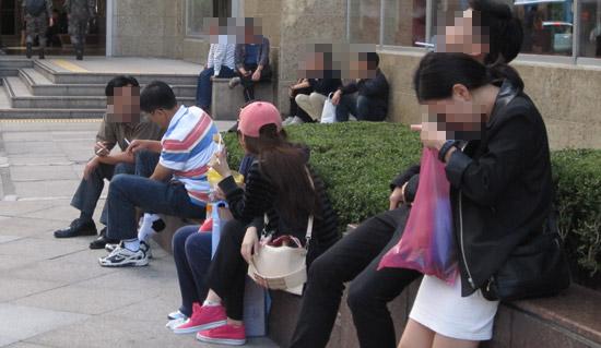 先月30日、ソウル小公洞のロッテ百貨店の前で、ショッピングを終えた中国人観光客が路上で喫煙している。