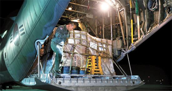 韓国政府は14日、フィリピン・タクロバンに救援物資を積んだ軍用機を派遣した。空軍第15特殊任務飛行団所属のC-130輸送機2機はフィリピン政府が要請した毛布・テント・衛生キット・浄水剤・非常食など救援物資20トンを載せ、この日午前、ソウル空港を離陸した。この日の1次支援に続き、今日(15日)も救援隊40人と救援物資10トンを積載したC-130輸送機2機が2次支援を行う。京畿道城南市のソウル空港の滑走路で、空軍の将兵がC-130輸送機に救援品を積んでいる。(写真=共同取材団)