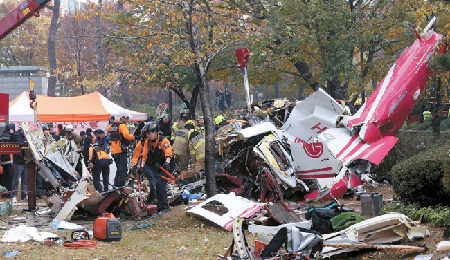 マンションに衝突し墜落したヘリコプターの残骸を検分する消防。