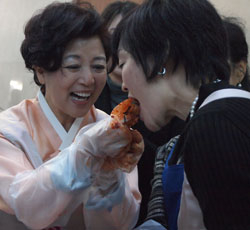 安倍昭恵さん(右)が大使夫人の沈載令さんが渡したキムチを試食している。(写真=駐日韓国大使館)