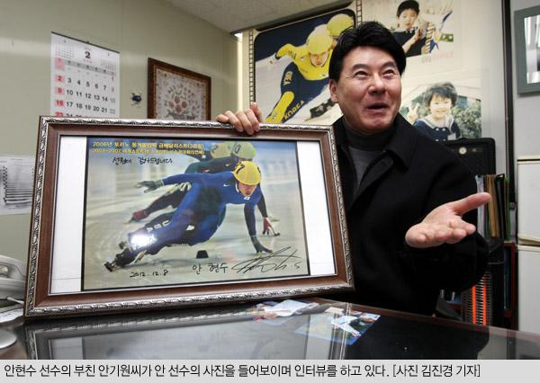 アン・ヒョンス選手の父親のアン・ギウォンさんがアン選手の写真を手にしながらインタビューに応じている。