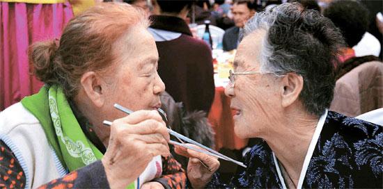 24日、金剛山ホテルで北側の妹パク・テホさん(81、右)が南側の姉パク・ナンホさんの口に食べ物を運んでいる。離散家族は今日(25日)午前に最後の対面をする。(写真=共同取材団)