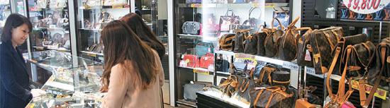 先月26日、ブランド店が並ぶ東京銀座の中古・並行輸入専門チェーン店「ブランドオフ」銀座店で、お客さんがブランド品の財布を選んでいた。
