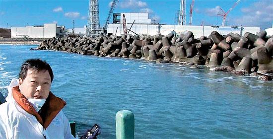 先月23日、福島第1原発沖に接近した中央日報の金玄基(キム・ヒョンギ)東京特派員が、撮影のために特殊マスクを脱いでいる。取材陣が堤防のそばに設置された消波ブロックに近づいた時、放射線測定機の数値は基準値の110倍に上がった。3年前の水素爆発当時の衝撃で崩れた3号機が見える。