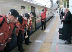 新幹線の掃除前に乗客にあいさつするテッセイの職員。