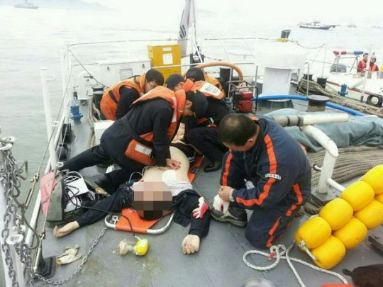 16日、珍島旅客船沈没事故の救助作業に駆けつけた海洋警察職員が、乗客に応急心肺蘇生術を施している。(写真=韓国海洋警察)