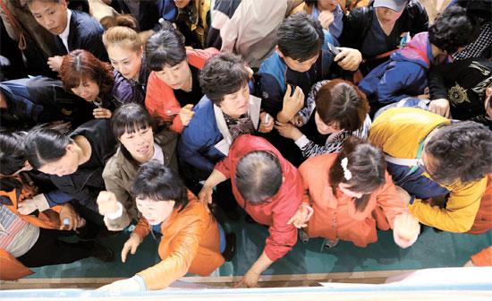 京畿道安山檀園高校の生徒の保護者が16日午後、全羅南道珍道の室内体育館に到着し、救助された人の名簿を確認している。