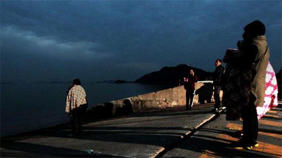 16日午前に沈没した「セウォル号」で行方不明になった乗客の家族が、海を見ながら救助の便りを待っている。