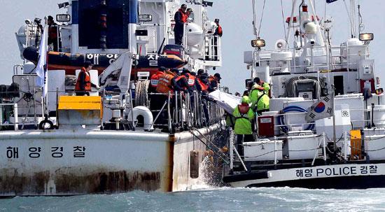 海洋警察の隊員が20日午後、「セウォル号」沈没事故海域の海上で遺体を収容している。官民軍合同救助チームの潜水要員は19日午後、初めて船体のガラス窓を割り、船内に入って3人の遺体を引き揚げた。救助チームが遺体を珍島パンモク港に運ぶ船に移している。