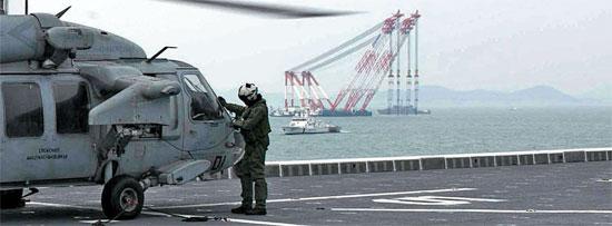 21日、クレーン船が見える事故海域に配置された独島艦で、米海軍ヘリコプターが離陸の準備をしている。韓米海軍は事故海域で共同救助作業を行っている。(写真=米国防総省)