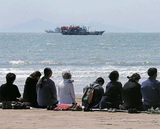 父母の日でもあった8日、全羅南道珍道(チョルラナムド・チンド)の彭木(ペンモク)港近くの砂浜で、正座をした市民が事故海域を見つめながら不明者の帰還と犠牲者を追慕する黙祷を捧げている。