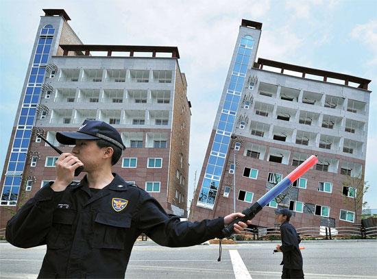 12日、忠清南道(チュンチョンナムド)の牙山(アサン)テクノバレー内に新築中だった7階建てオフィステル(事務所兼住居用)建物(右側)が20度ほど傾いている。この日午前8時ごろ、傾いた同建物に対して警察と消防当局は崩壊の危険が高いと判断して近くの道路などを立ち入り禁止にした。この建物は7階建ての高さで建築面積1647平方メートルの複合建築物だ。2013年7月に着工し、今月31日の竣工を控えていたため入居者はまだいなかった。
