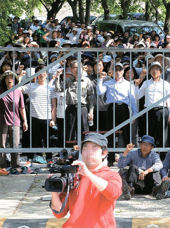 13日、京畿道安城市にあるクムスウォンの入口に救援派信徒らが清海鎮海運会長の長男テギュン氏に対する逮捕令状の執行を阻むために集結している。