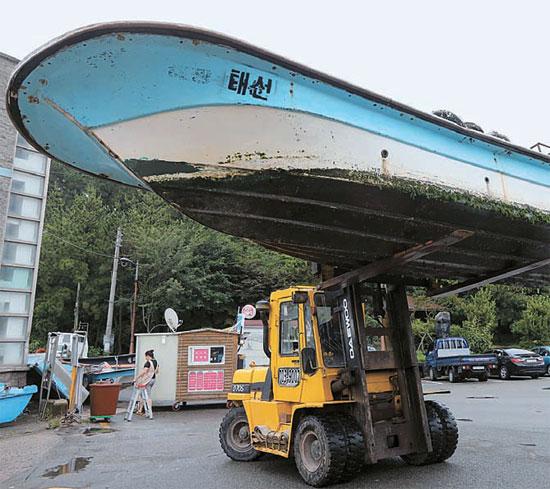 7日、釜山海雲台区の松亭漁村契の漁民が小型船舶を陸上に移動させている。