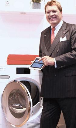 5日にドイツで開かれた家電見本市IFA2014に参加したミーレのラインハルト・ジンカン会長がタブレットPCでドラム洗濯機を作動させている。創立115年を迎えたミーレはスマートホームである「ミーレアットホーム」を初めて公開した。(写真=ミーレ)