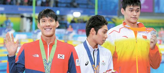 朴泰桓(183センチ、左)が仁川アジア競技大会自由形男子200メートルの表彰式の後、観客に手を振っている。1位は日本の萩野公介(175センチ、真ん中)、2位は中国の孫楊(198センチ)で、朴泰桓は3位だった。
