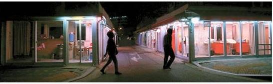 20日夜、灯りがついたソウル典農洞の俗称「清凉里588」。大通りにつながる入り口には「開発を歓迎する」と書かれた懸垂幕が設置されている。東大門区庁は最近、この地域に高層ビルを建設し、駅前の商業地域として再開発する事業計画を承認した。