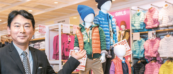19日にユニクロ銀座店子ども服売り場でユニクロの中嶋修一商品本部長が子ども用手洗いパデットジャケットについて説明している。(写真=ユニクロ)