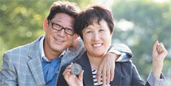 黄載鈞の父ファン・ジョンゴンさん(左)と母ソル・ミンギョンさん。ソルさんが1982年ニューデリーアジア競技大会で獲得した金メダルを持って笑っている。
