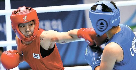 パク・ジンア(25、保寧市庁、左)が1日、仁川アジア競技大会女子ボクシング60キロ級の決勝戦で、尹軍花(中国)を攻撃している。