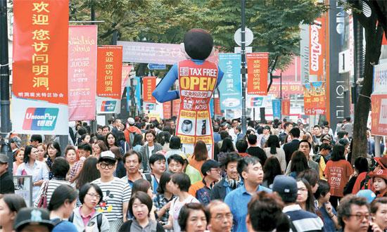 中国の国慶節連休が始まった1日、ソウル・明洞には中国人観光客を歓迎する中国語で書かれた赤い垂れ幕があちこちに掲げられている。電子商店街の販促要員の背中にも中国語が書かれている。