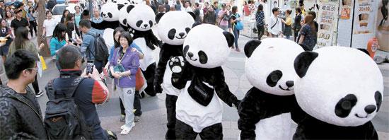 中国国慶節の1~7日にソウルを訪れた中国人観光客が大きく増え流通企業が久し振りに笑った。ロッテ・新世界・現代の百貨店3社での中国銀聯カード使用額は昨年同期より62~91%急増した。高価ブランド品だけでなく中低価格の衣類・化粧品の売り上げも大きく膨らんだ。写真は新世界百貨店が中国人観光客を誘致するため明洞で行ったパンダパレード行事。