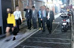 18日夜、ソウル明洞駅付近の地下鉄換気口の上を人々が通過している。
