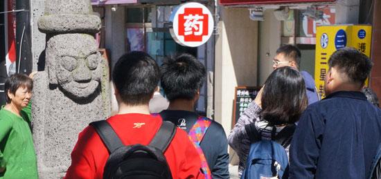 済州島で中国人観光客が最も多く集まる所に挙げられる済州市蓮洞の宝健通り。中国語の簡体字が書かれた看板を掲げた店のそばに済州の象徴であるトルハルバンが並んでいる。