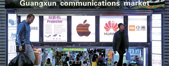 情報通信技術(ICT)産業の新しいメッカに浮上している深センでは「モバイル」競争が激しい。世界の主要スマートフォンメーカーと中国現地企業が市場の主導権を握るため角逐している。昨年12月2日、深センの大型IT流通センター「華強北」の電子商店街入り口。通行人に隠れたサムスン電子のロゴが、シャオミ・華為など中国企業の激しい挑戦に直面し、しだいに居場所を失っていく韓国ブランドの姿を象徴するようだ。