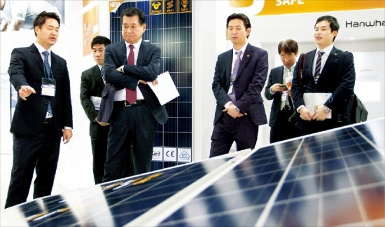 ハンファQセルズのナム・ソンウ社長(左から2番目)が東京ビックサイトで今月25日に開幕したワールドスマートエネルギー展示会で職員と共に太陽光モジュール展示作品を見回っている。(写真=ハンファグループ提供)