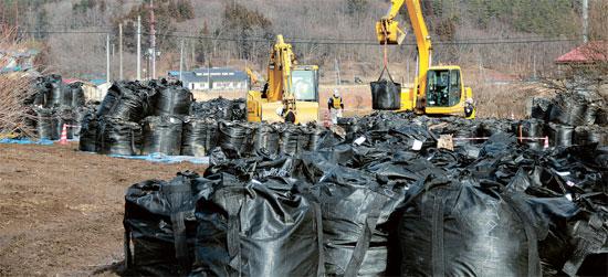 先月25日、福島県の飯館村では放射線汚染の可能性が高い地表5センチの汚染土を除去する作業の真っ最中だった。「放射線汚染土」を1トンごとにまとめた袋が積まれている。