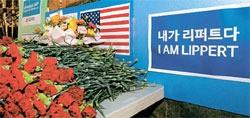 在韓米国大使館の前に6日、リッパート大使の快癒を祈願する花束が置かれている。後ろに「私はリッパート」という文字が見える。