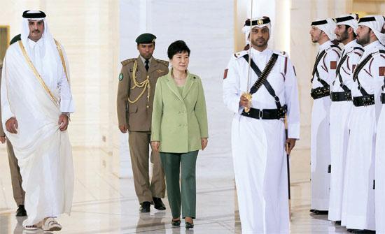朴大統領が8日(現地時間)、カタールの首都ドーハのエミリ・ディーワン宮殿に到着し、タミム首長(左)と儀仗隊を閲兵している。朴大統領は歓迎式後の首脳会談で、2022年カタールワールドカップ(W杯)のインフラ構築事業(合計1000億ドル投入予定)に対する韓国企業の参加を要請した。