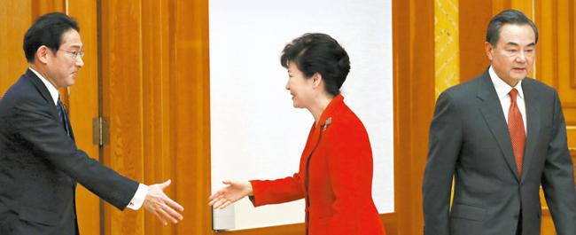 朴槿恵大統領が21日、青瓦台で就任後初めて会う日本の岸田外相(左)と握手を交わしている。右は中国の王外相。(写真=青瓦台写真記者団)